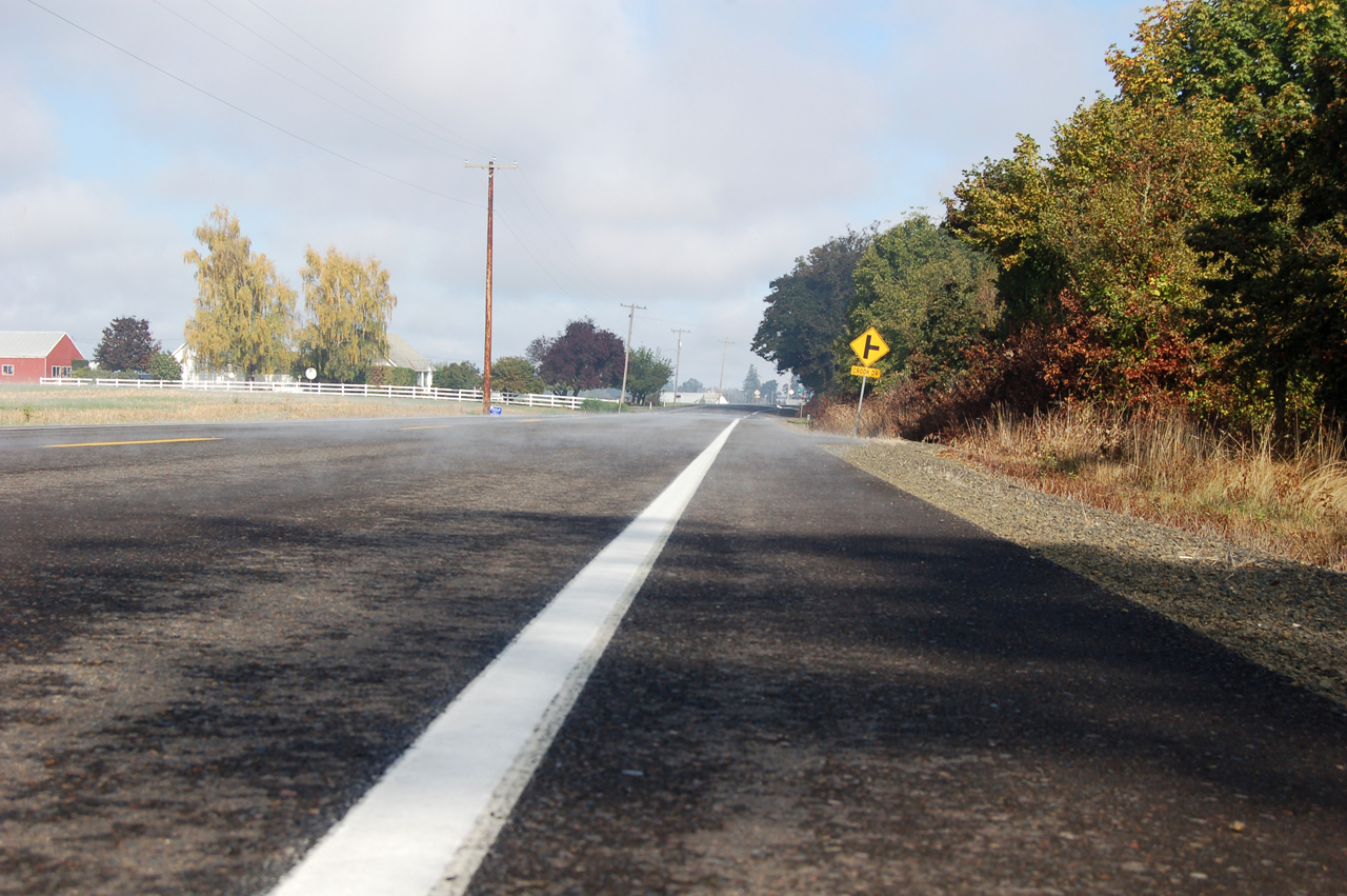 Fog burns off and steam comes off the road